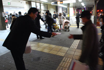 街頭で電話労働相談ビラ入りのティッシュを配る行動参加者