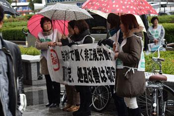 雨が降るなか、横断幕で街ゆく人々に訴えた